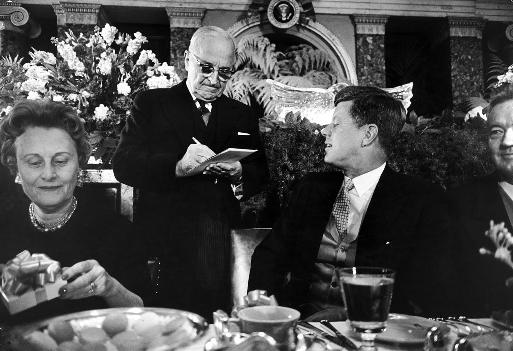 Harry Truman signs an autograph for John Kennedy during the inaugural luncheon.