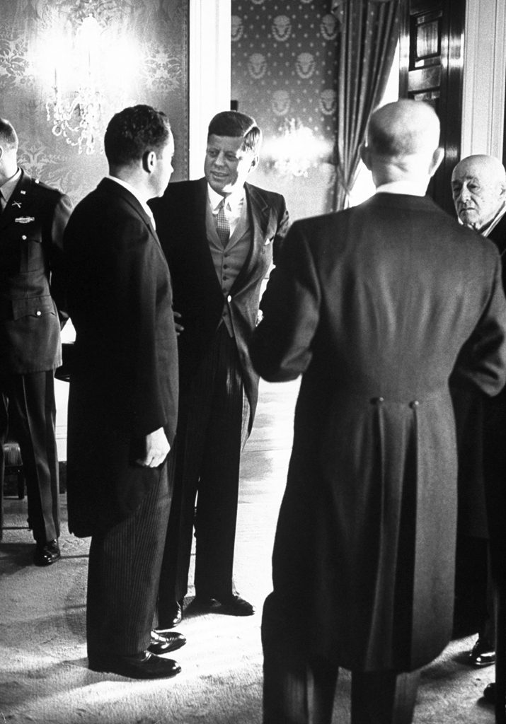 Richard Nixon and John Kennedy speak during a receiption after JFK's inauguration