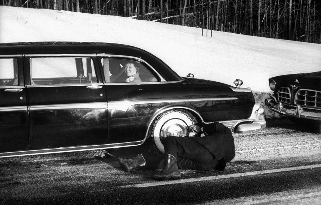Dwight D. and Mamie Eisenhower wait as their driver takes the snow chains off their limo's tires.