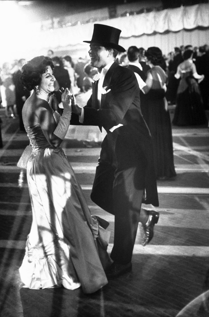 A woman in a gown and a man in a suit with a top hat dance at one of the ball's celebrating John Kennedy's inauguration.