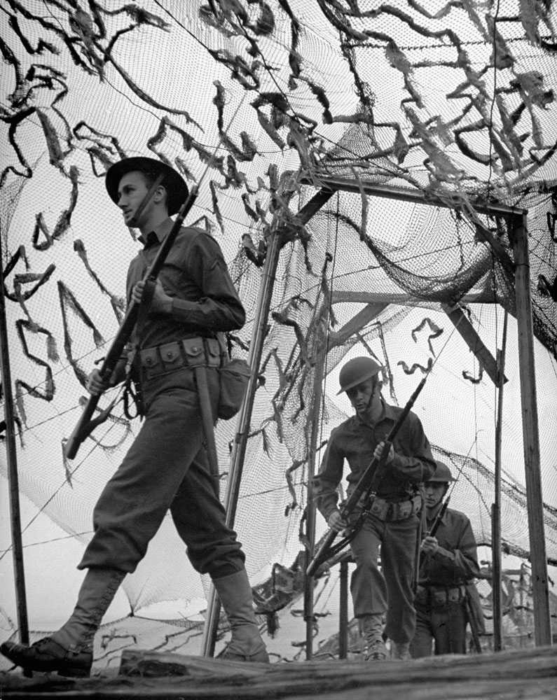 American soldiers drill under camouflage netting, which screens a coastal defense position, in 1942, shortly after the Japanese attack on Pearl Harbor.
