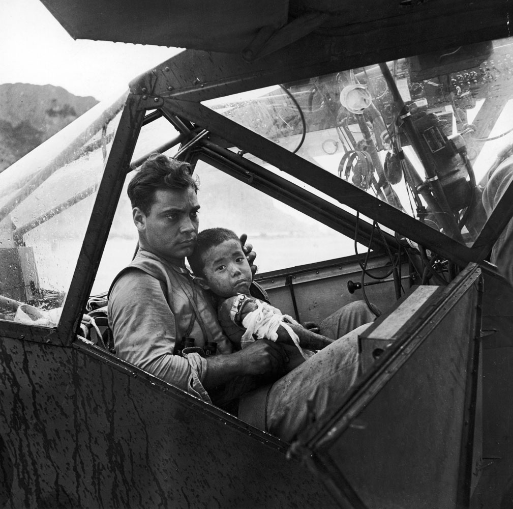 An American soldier holds a wounded Japanese boy in an airplane on Saipan as they await a flight to the nearest field hospital in 1944.