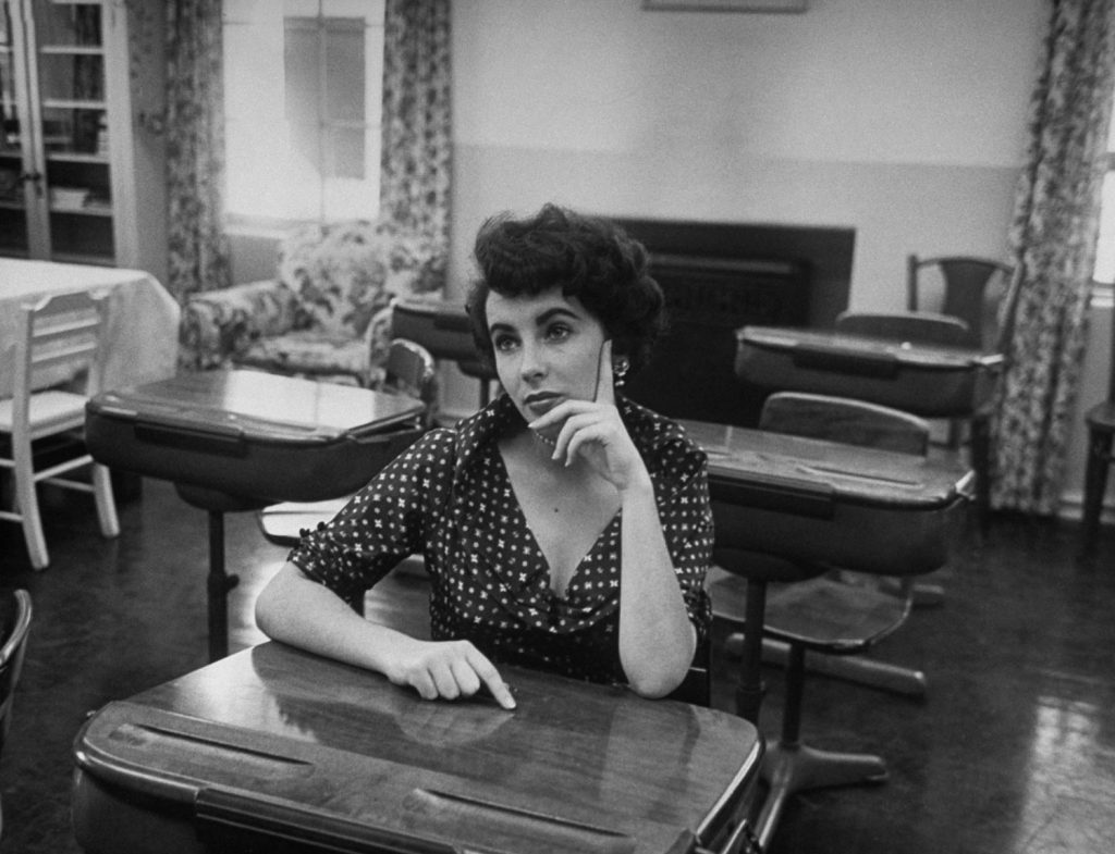 Elizabeth Taylor sits at a desk in a classroom at Hollywood's University High School in 1950.