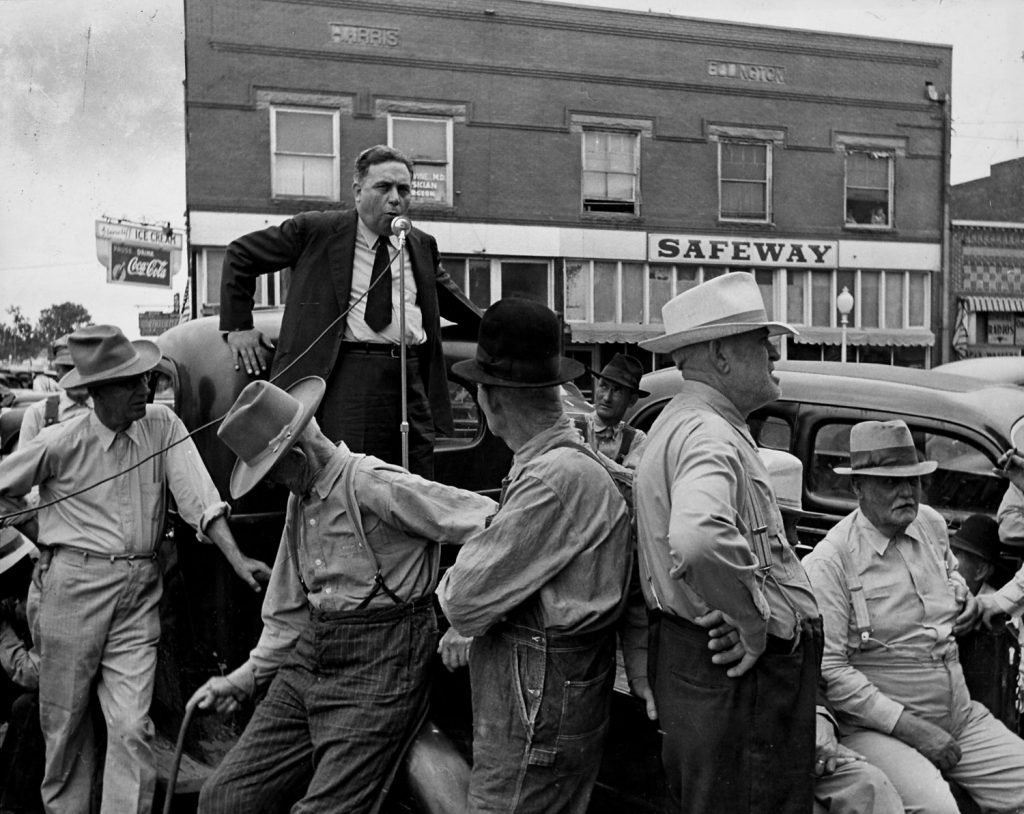 Gomer Smith talks to small gathering on street from bed of feed truck, Wagoner, Oklahoma in June 1942.