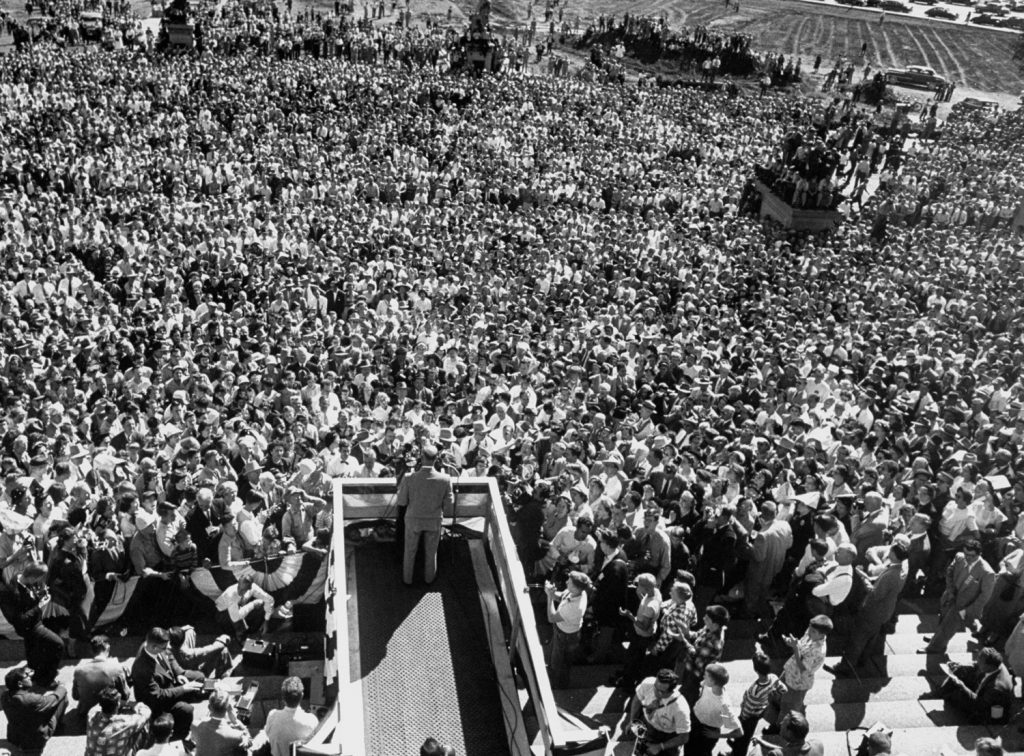 A photo from above of General Dwight D. Eisenhower standing at a lectern delivering a speech during a campaigning whistle stop tour of the mid-west in September 1952. There are hundreds of people in the crowd.