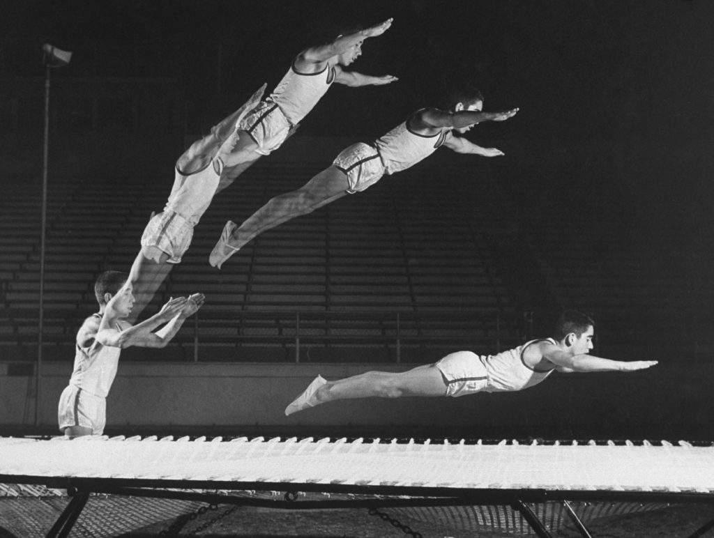 A multiple exposure shot of a gymnast jumping on a trampoline in 1960.