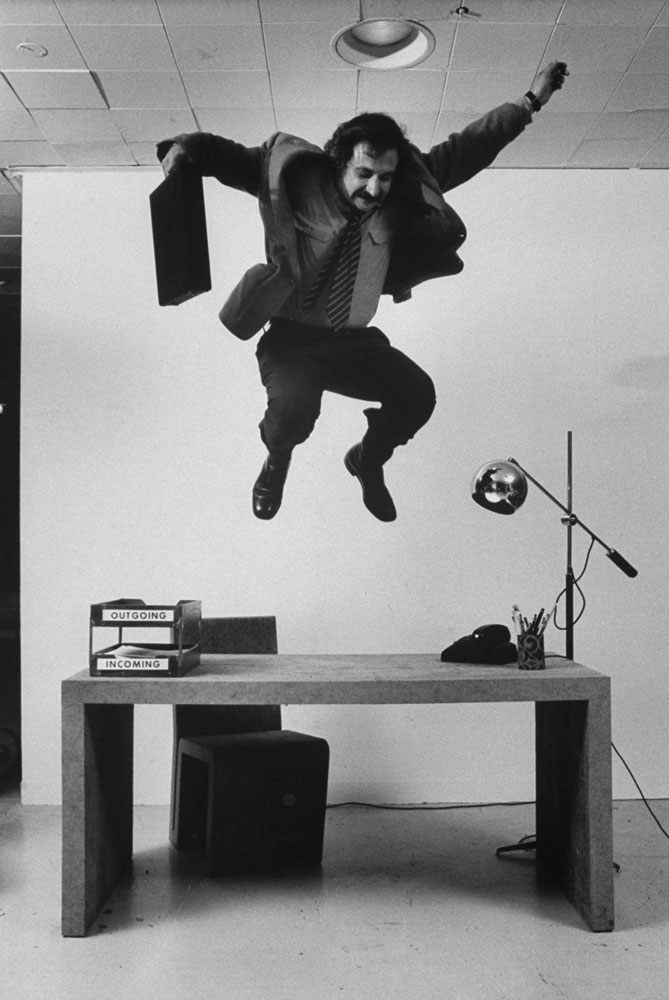 Frank Gehry jumps on a desk   part of his line of cardboard furniture   in 1972.