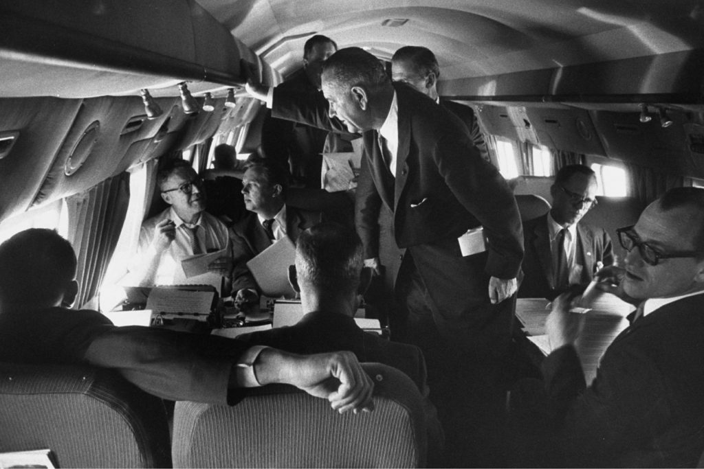 Senator Lyndon B. Johnson (D-Texas) talks with staff and reporters while on a plane in April 1960, before accepting John Kennedy's offer to be his running mate.