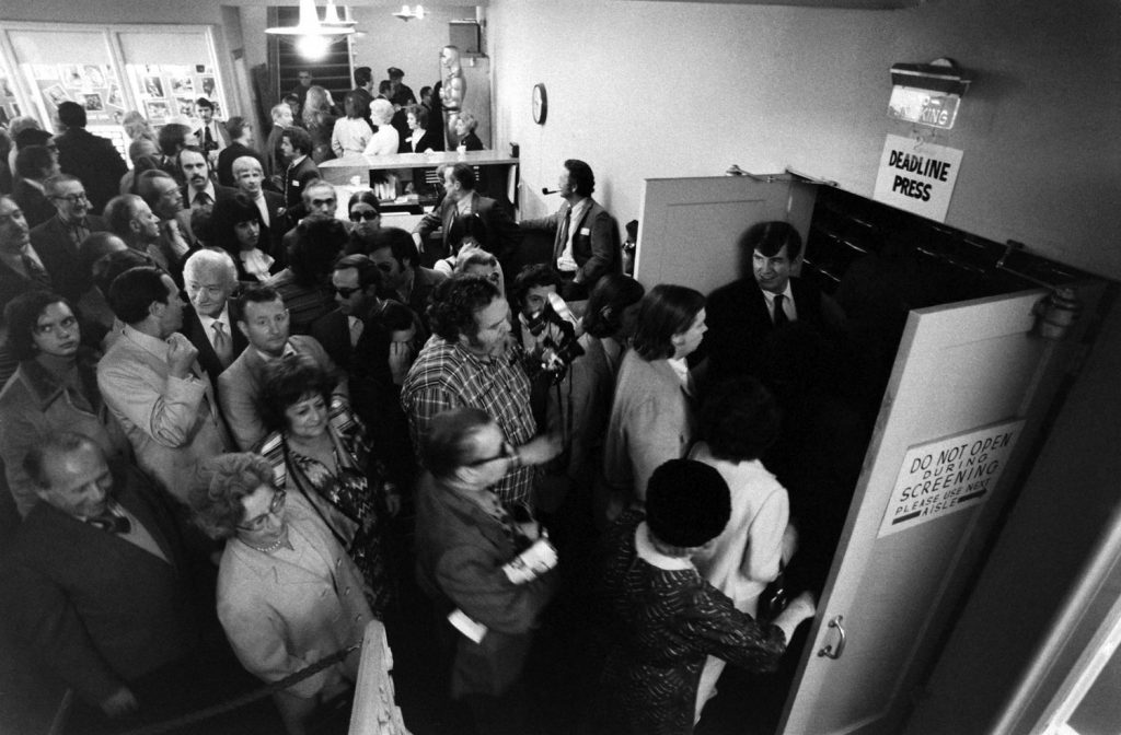 Members of the Academy enter an auditorium for a screening of an Oscar nominated film, 1972.