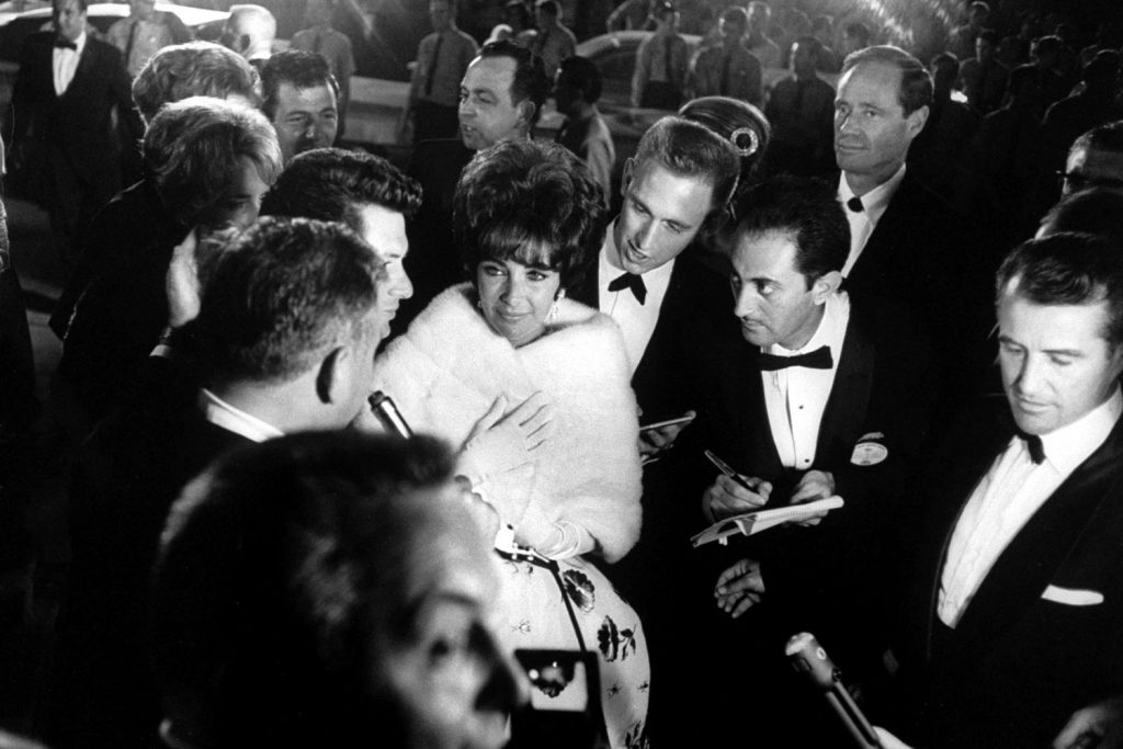 Elizabeth Taylor walks through a crowd of admirers at the Oscars in 1961.