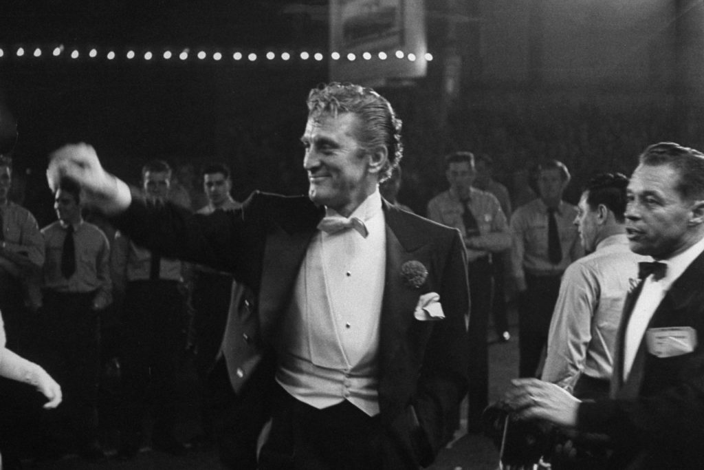Kirk Douglas, elegant in white tie, smiles and waves as he enters the RKO Pantages Theater in 1954.