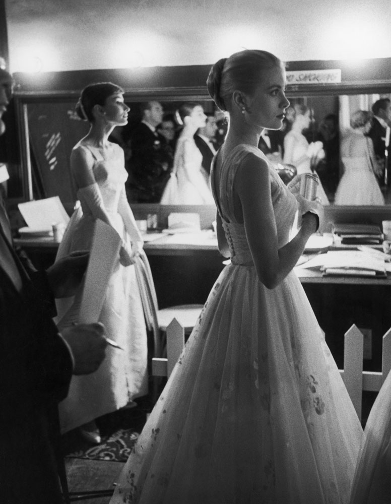 Audrey Hepburn and Grace Kelly wait backstage at the RKO Pantages Theatre during the 1956 Academy Awards.