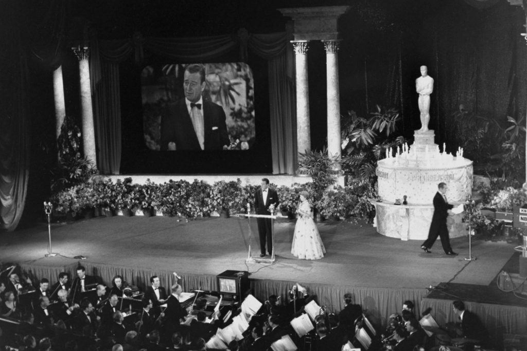 John Wayne accepts the Best Director Oscar from Olivia DeHavillan for an absent John Ford during the 25th annual Academy Awards in 1953