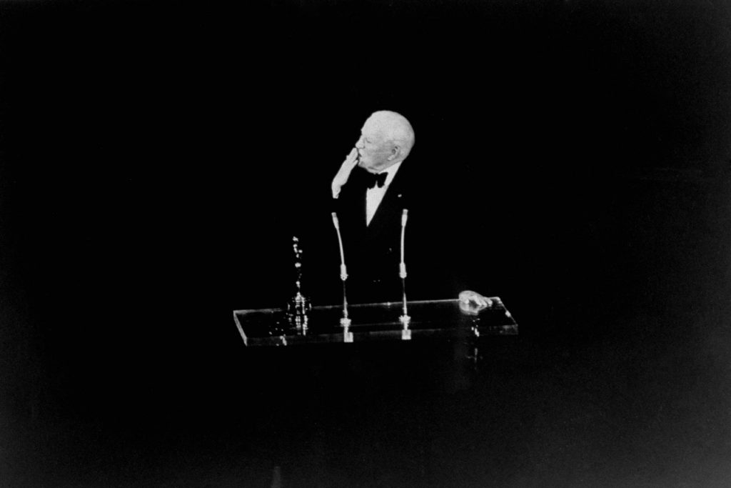 """The great, inimitable Charlie Chaplin   who had been living in self-imposed exile in Switzerland for two decades   blows a kiss to the crowd while accepting an honorary Oscar in 1972 for """"the incalculable effect he has had in making motion pictures the art form of this century."""""""