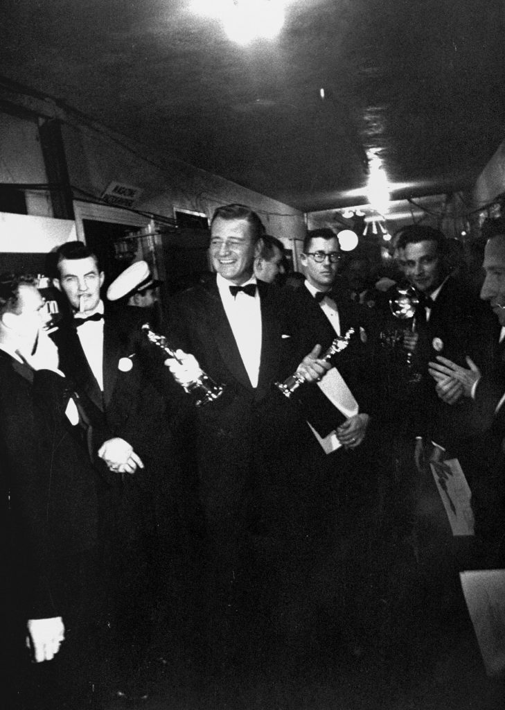 John Wayne holds Oscars for Gary Cooper and John Ford (Best Actor for High Noon) and Best Director for The Quiet Man, respectively) backstage at the 25th Academy Awards at the RKO Pantages Theatre, Hollywood, 1953.