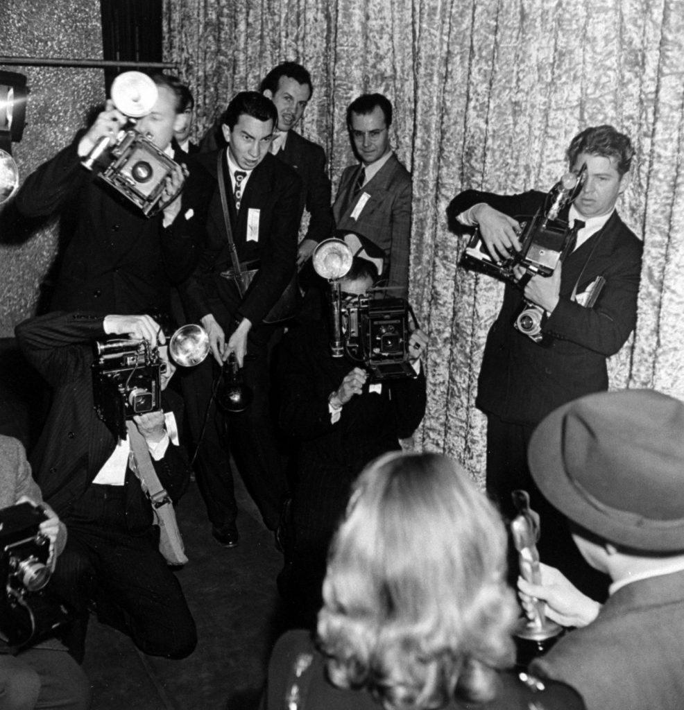 Photographers snap their cameras Oscar winners Ingrid Bergman and Bing Crosby