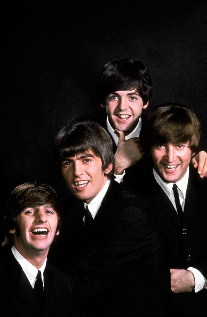 John Lennon, Paul McCartney, George Harrison, and Ringo Starr pose in a portrait on a black backdrop in January 1964