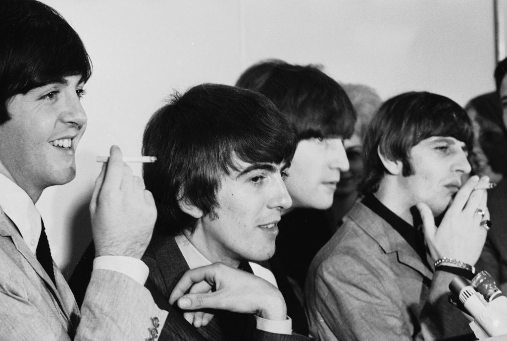The Beatles joke and smoke at a press date in August 1964.