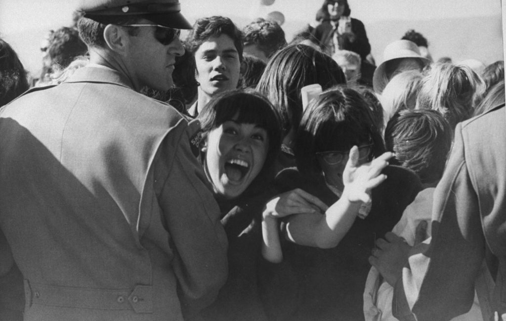 Police hold back a crowd of fans at the Los Angeles airport in August 1964.