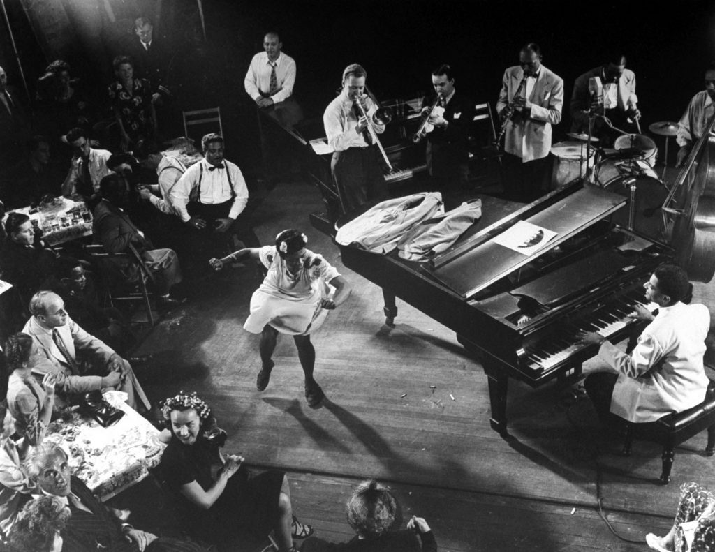 "Pearl Primus performs to ""Honeysuckle Rose"" as played by an all-star group consisting of Teddy Wilson (piano), Lou McGarity (trombone), Sidney Catlett (drums), Bobby Hackett (trumpet) and John Simons (bass)."
