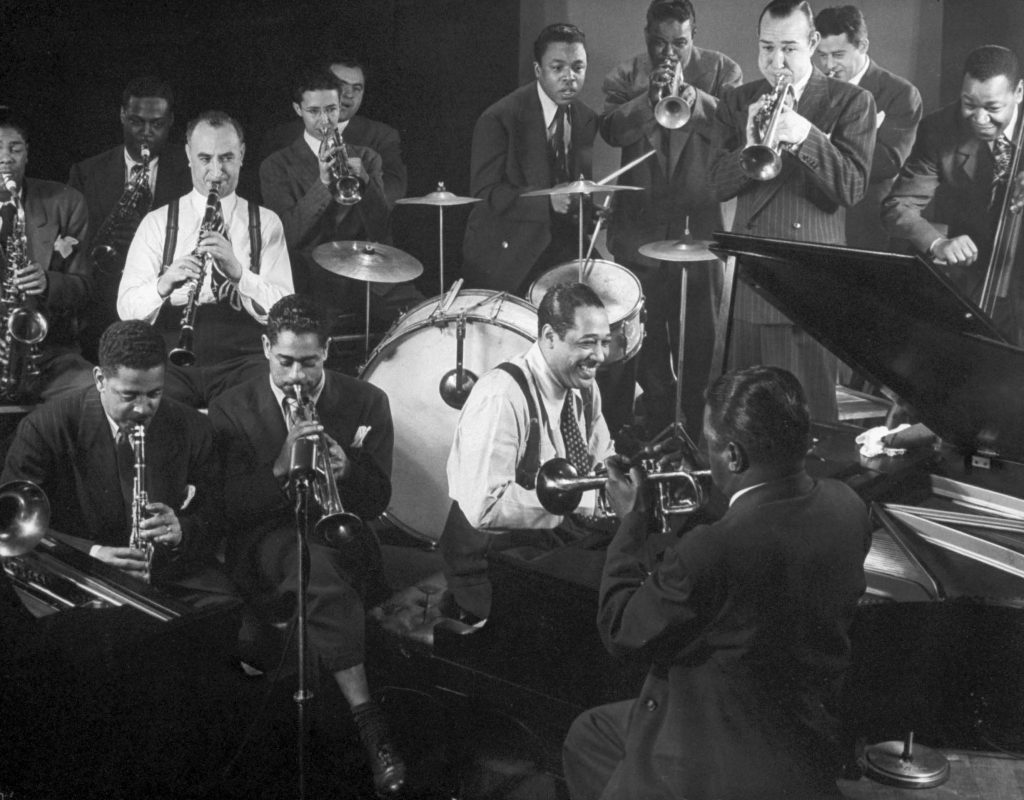 Duke Ellington at the piano as Dizzy Gillespie (seated behind Ellington) and others swing, 1943.