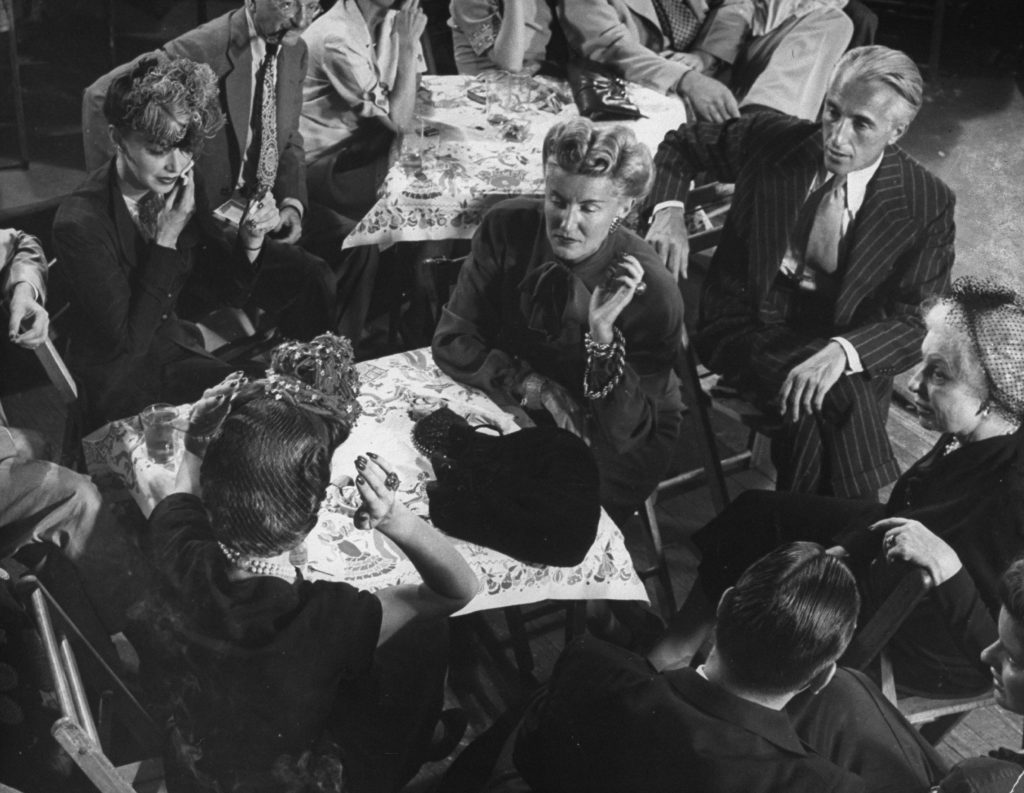 Conde Nast president Iva Patcevitch (in striped suit), Vogue editor-in-chief Edna Woolman Chase (far right, in hat) and other media types hang out at Gjon Mili's studio during a jam session, 1943.