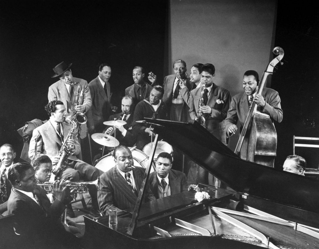 Jazz jam session, including Lester Young (standing, in hat) on saxophone and Count Basie at the piano, 1943.