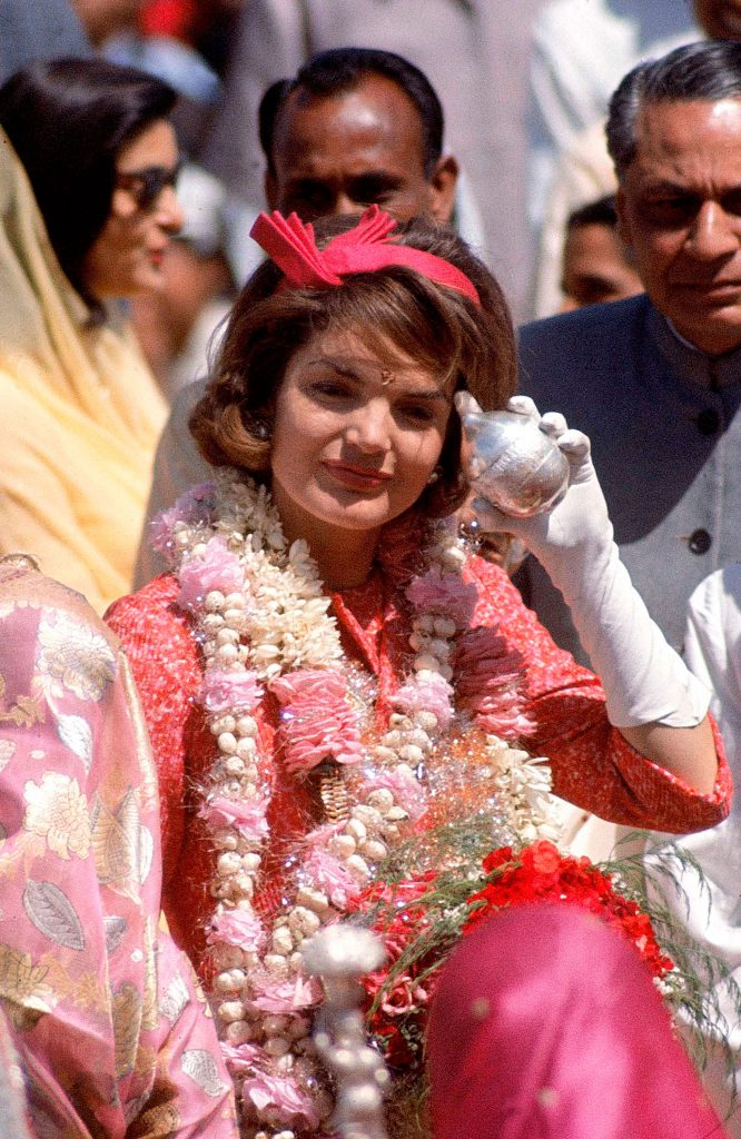 In a sea of Indian saris, Mrs. Kennedy and Rajasthan's governor move through Jaipur airport. On her forehead is the Rajasthani mark of luck and respect, the tika. Her silver-encased coconut also honors the occasion