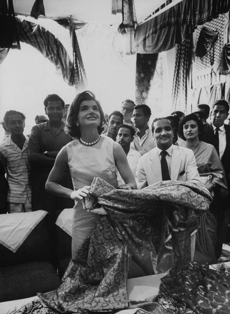 On a side trip to a textile showroom in Banaras, Mrs. Kennedy wore a sleeveless pink unbelted and high-waisted sheath of linen-like silk by New York designer Donald Brooks. Covered buttons up the side.