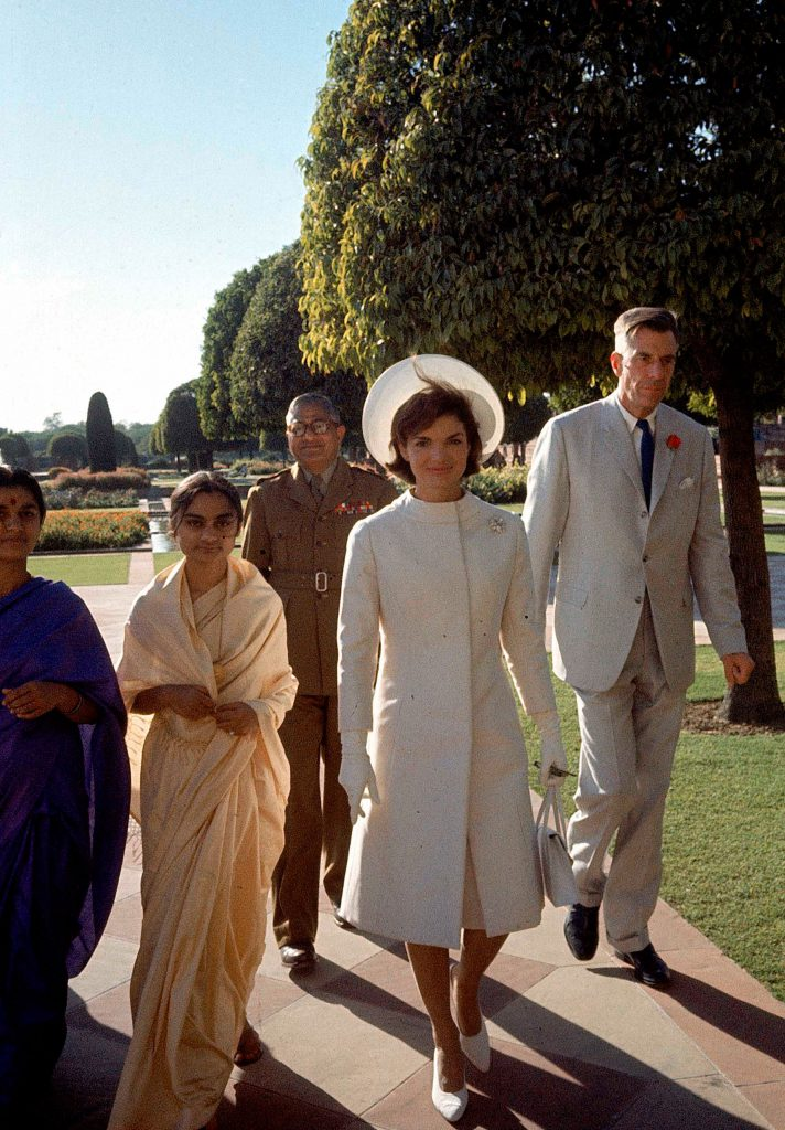First Lady Jackie Kennedy, center, in a white coat and hat walks with Ambassador John Galbrath, right, in India in 1962.