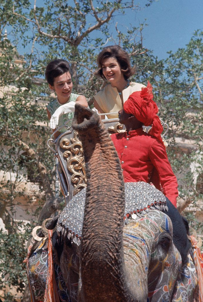 At Jaipur, sitting in an elaborately carved howdah, Jackie and her sister [Lee Radziwill] ride on a trumpeting female elephant, newly painted and spangled for the show.