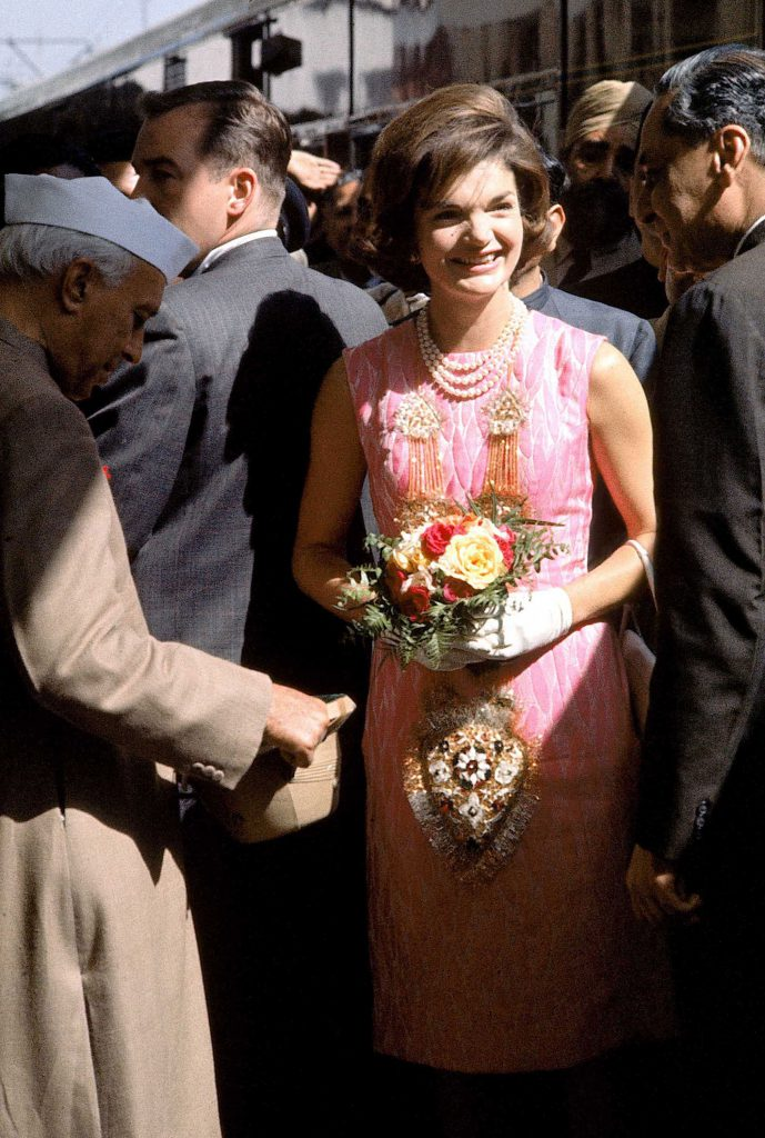 First Lady Jacqueline Kennedy wears a pink dress and three-stranded pearls during her visit with Indian leader Jawaharlal Nehru, left, and Ambassador to the U.S., Braj Kumar Nehru.