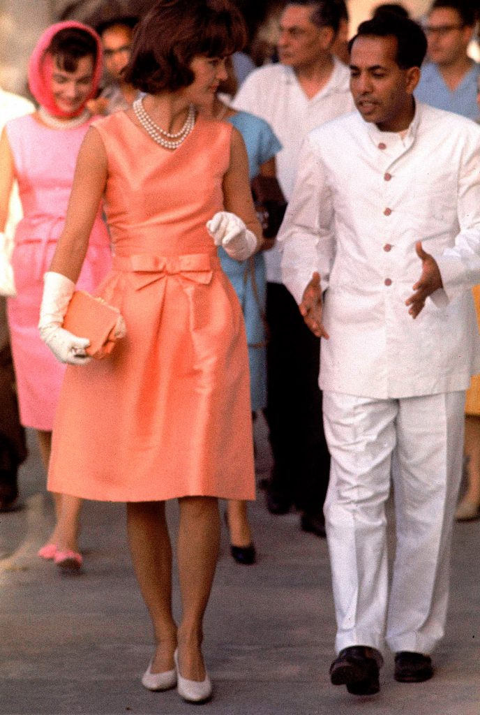 "In fitted silk apricot dress, Jackie walks through crowds at Udaipur, where she was given a noisy reception."" She walks with the Maharaj of Mewar, left, during her visit in 1962."