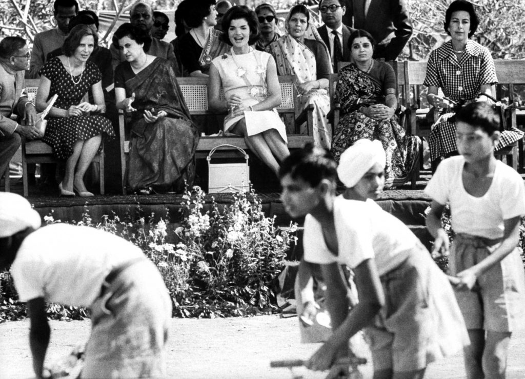 Mrs. Kennedy, center, and Mrs. Indira Gandhi, third from left, attend a sporting event on the First Lady's tour of India in March 1962.