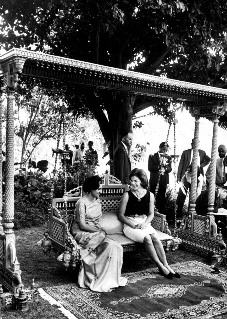On a carved wooden swing in the prime minister's garden, the First Lady sits and talks with Mrs. Indira Gandhi, Nehru's daughter and the former president of the ruling Congress party of India.