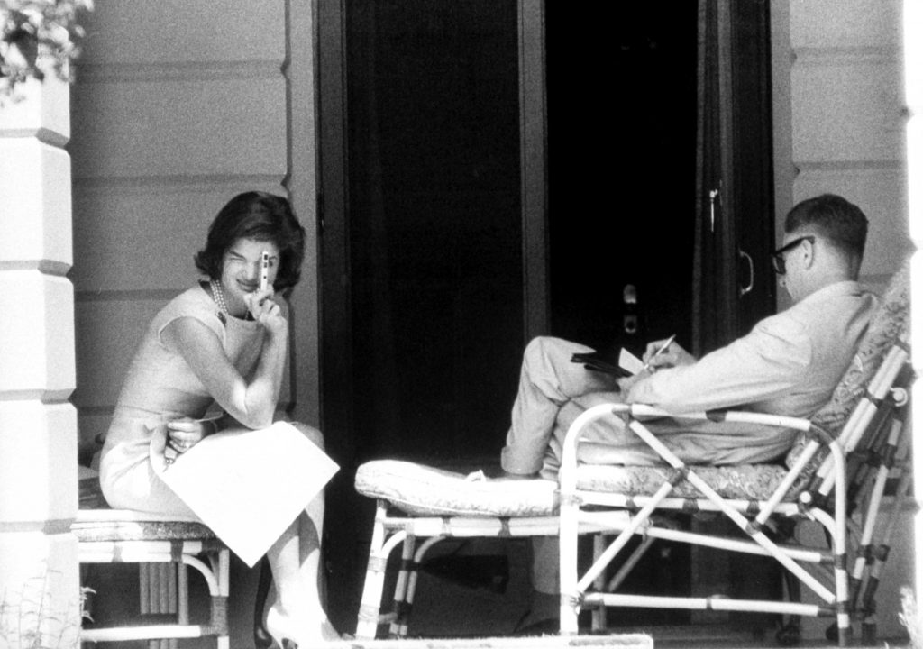 On veranda outside her room at the residence of Prime Minister Nehru, Mrs. Kennedy turns her miniature camera on photographers. Beside her, Ambassador Galbraith busies himself with his notes