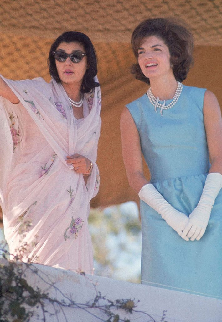 First Lady Jackie Kennedy, right, in blue sheath dress and white gloves watches a polo match with Maharani of Jaipur, Gayatri Devi, on a visit to India in March 1962.