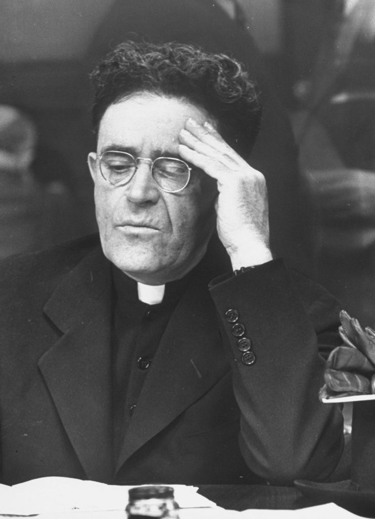 A priest at an Internal Revenue information center in New York in 1944.