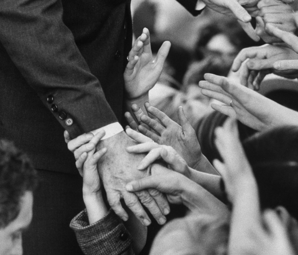 Sen. Robert F. Kennedy shakes hands with admirers in October 1966.