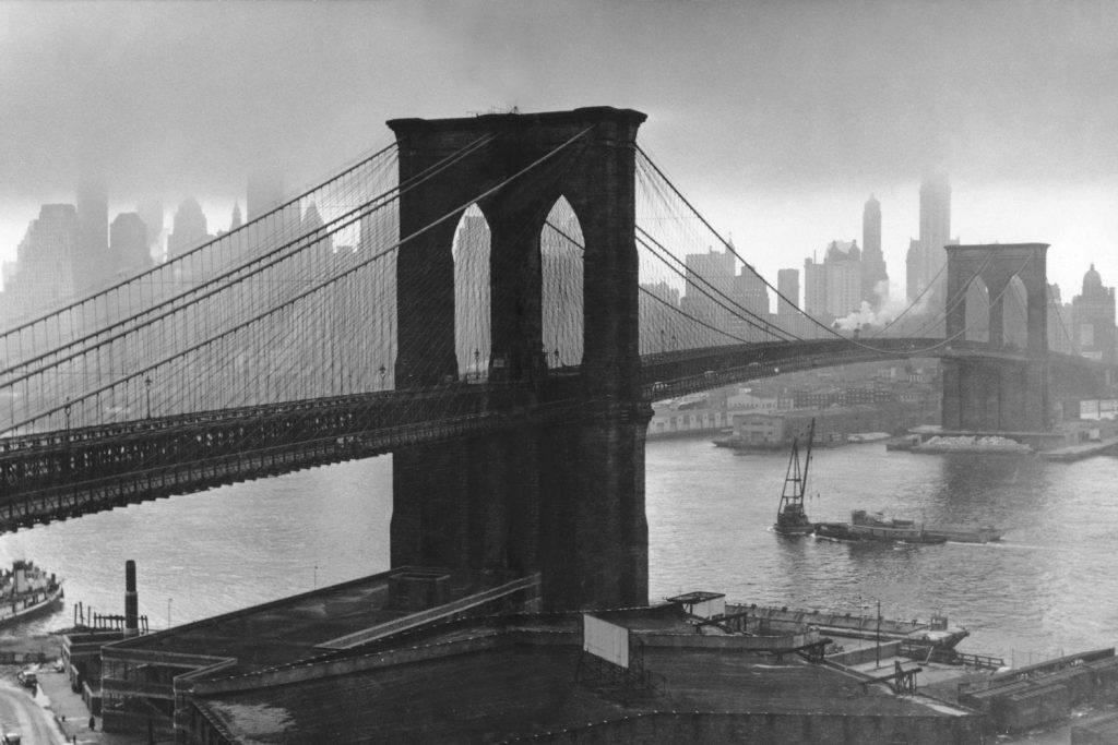 Stormy sky hovers over the Brooklyn Bridge and the ghostly skyscrapers of Manhattan's financial district in March 1946.