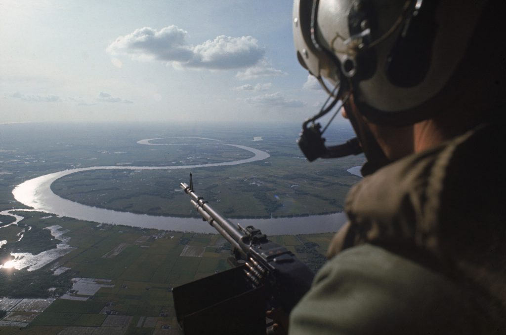 Machine gunner in helicopter on patrol over the Mekong Delta in 1967.