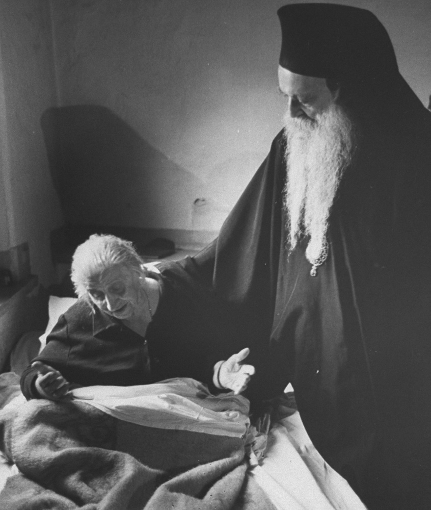 Patriarch Athenagoras I, Archbishop of Constantinople (Istanbul), Eastern Orthodox, visits a sick member of the church.