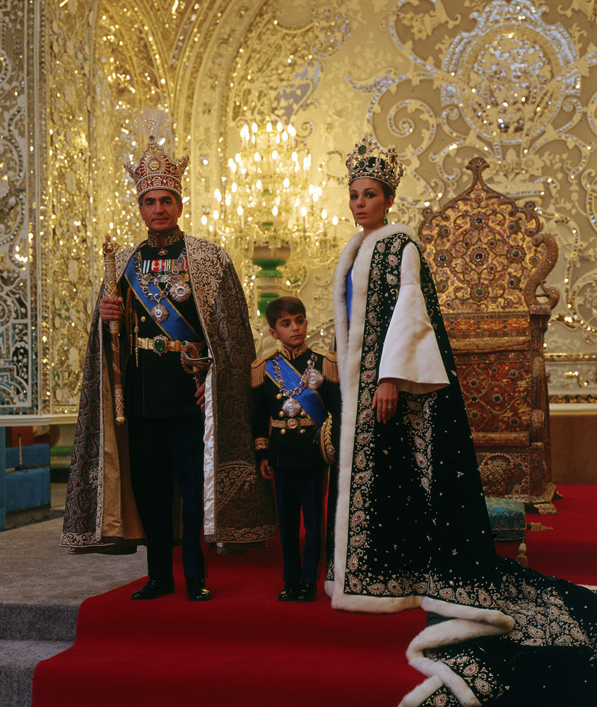 Shah of Iran, Mohammad Shah Pahlavi, posing with his son Prince Reza and wife Farah, wearing crown jewels and embroidered robes, following his coronation in 1967.
