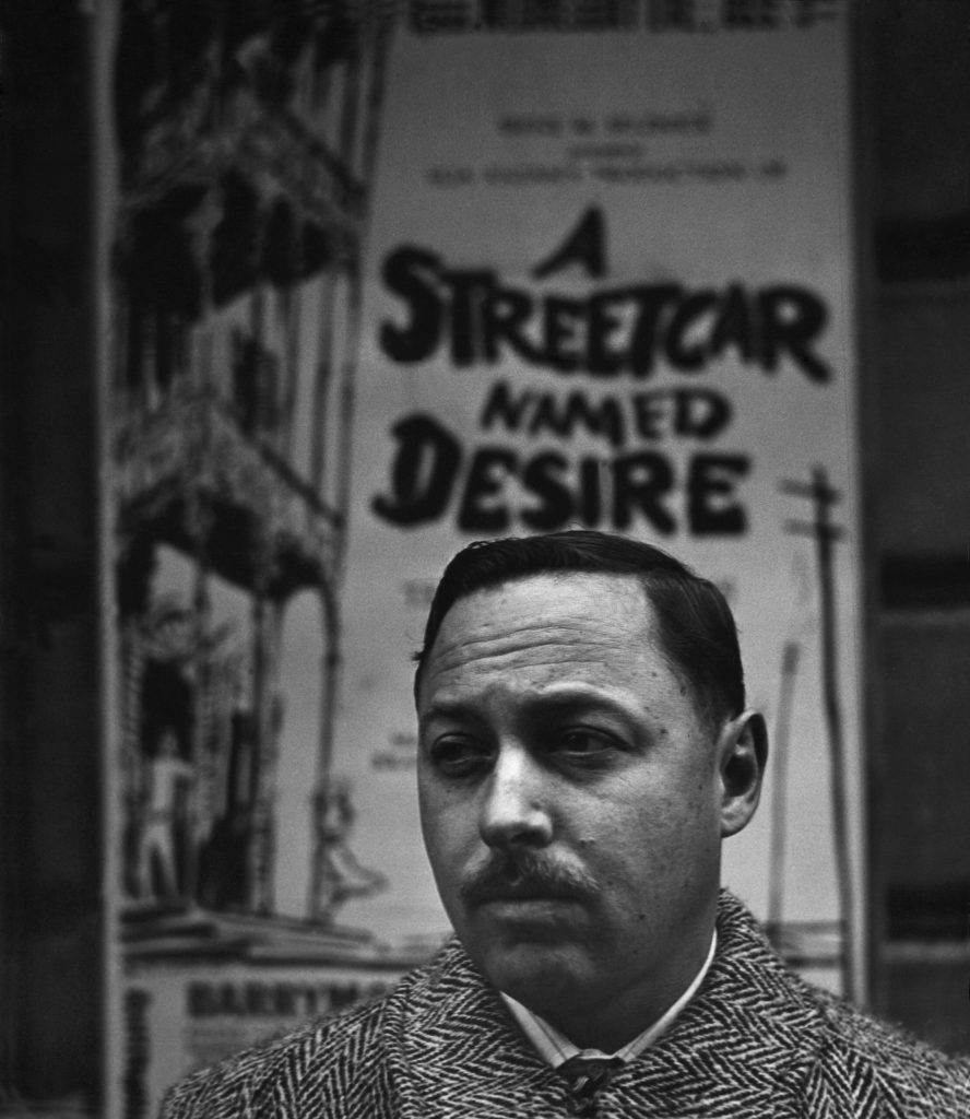 Tennessee Williams stands in front of a poster advertising his play, A Streetcar Named Desire, in New York in 1948.