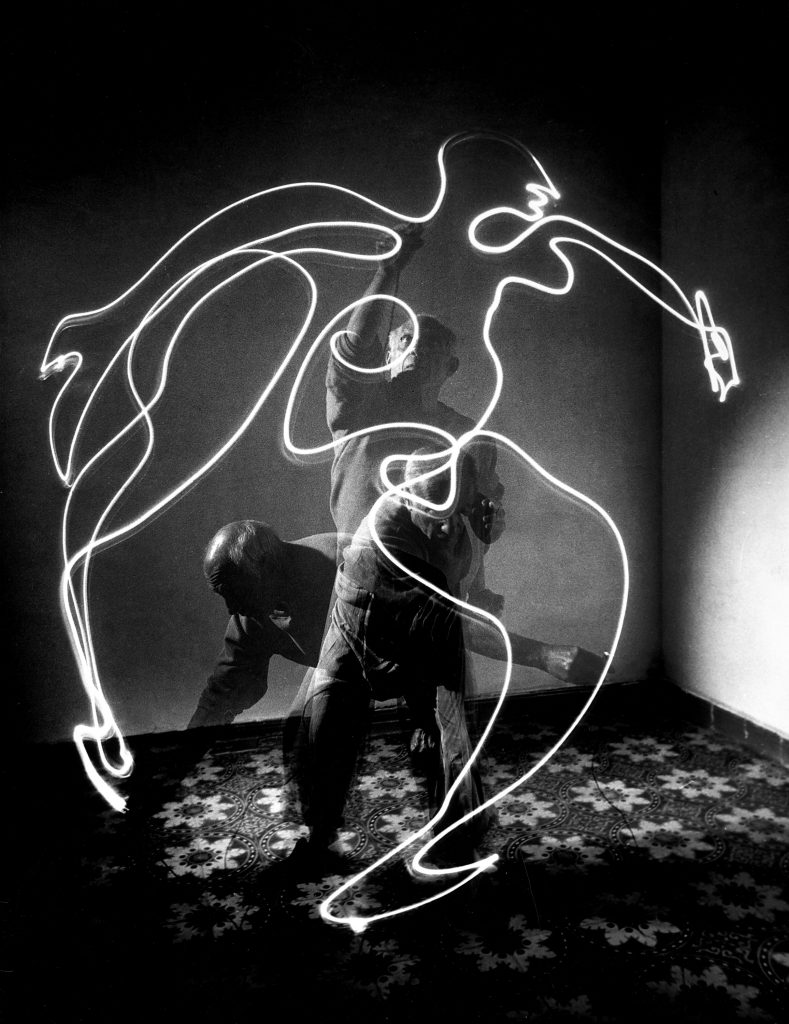 """Multiple exposure photograph of Pablo Picasso using a small flashlight to """"draw"""" a figure in the air in 1949."""