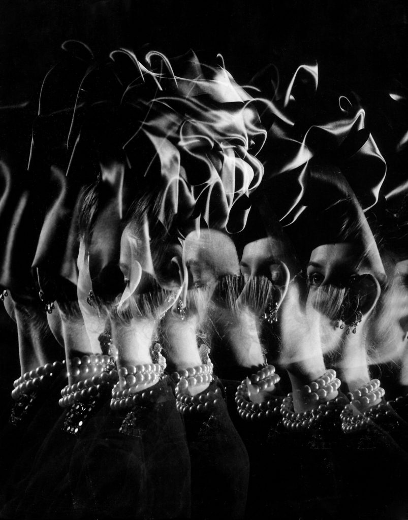 Stroboscopic image of the head and shoulders of a model wearing an elaborate hat and jewelry, 1946.