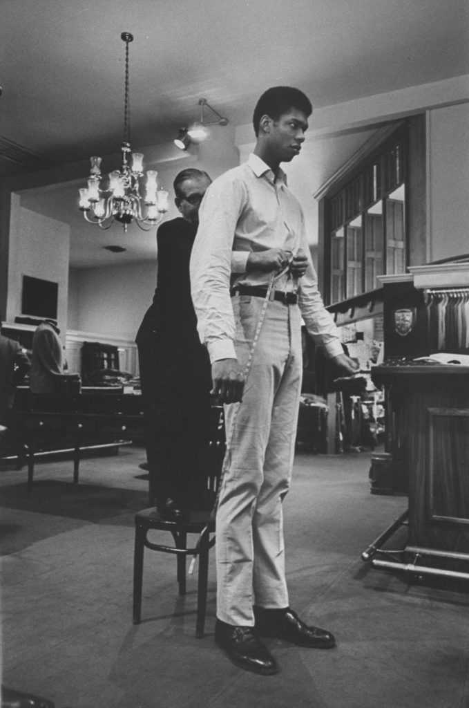 Seven-foot, two-inch Lew Alcindor (later Kareem Abdul-Jabbar, here being fitted for trousers with a 51-inch inseam in 1967) left his native New York for UCLA, where he helped the Bruins win a record 88 games in a row and three national titles.