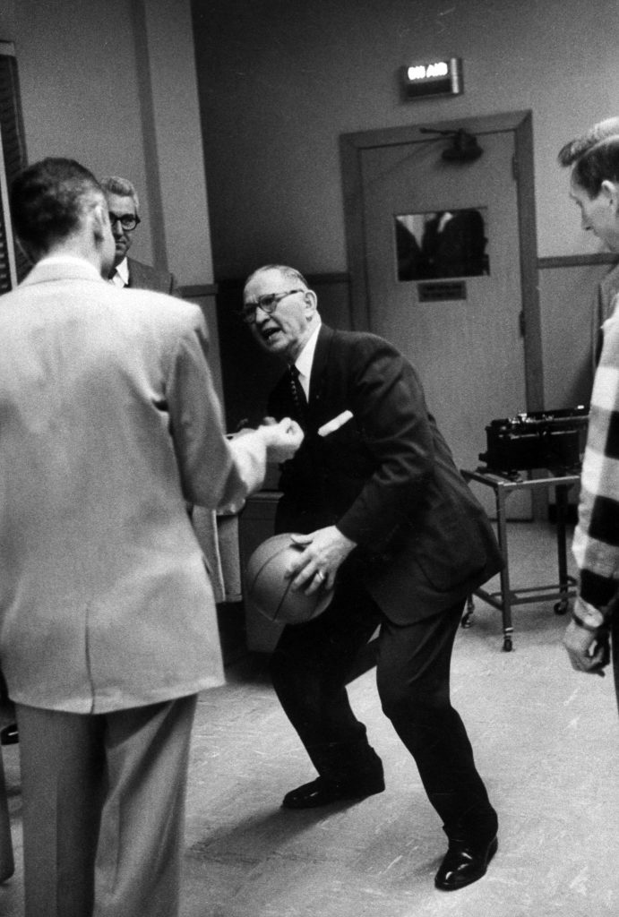 "The legendary Kansas coach Forrest Allen, nicknamed ""Phog,"" is often referred to as the ""Father of Basketball Coaching,"" although these days not too many people mention him when discussing the greatest college coaches in history. Allen (here demonstrating some sort of funky move in 1957) coached Dean Smith; he recruited Wilt Chamberlain to Kansas; the Jayhawks' famous Allen Fieldhouse is named for him, and a banner hanging in the fieldhouse reads, ""Pay heed all who enter, beware of the Phog."""