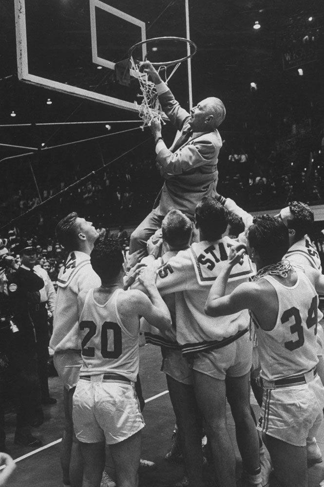 "Legendary North Carolina State Wolfpack coach Everett ""The Gray Fox"" Case cuts down the net after winning the Dixie Classic title in 1959."