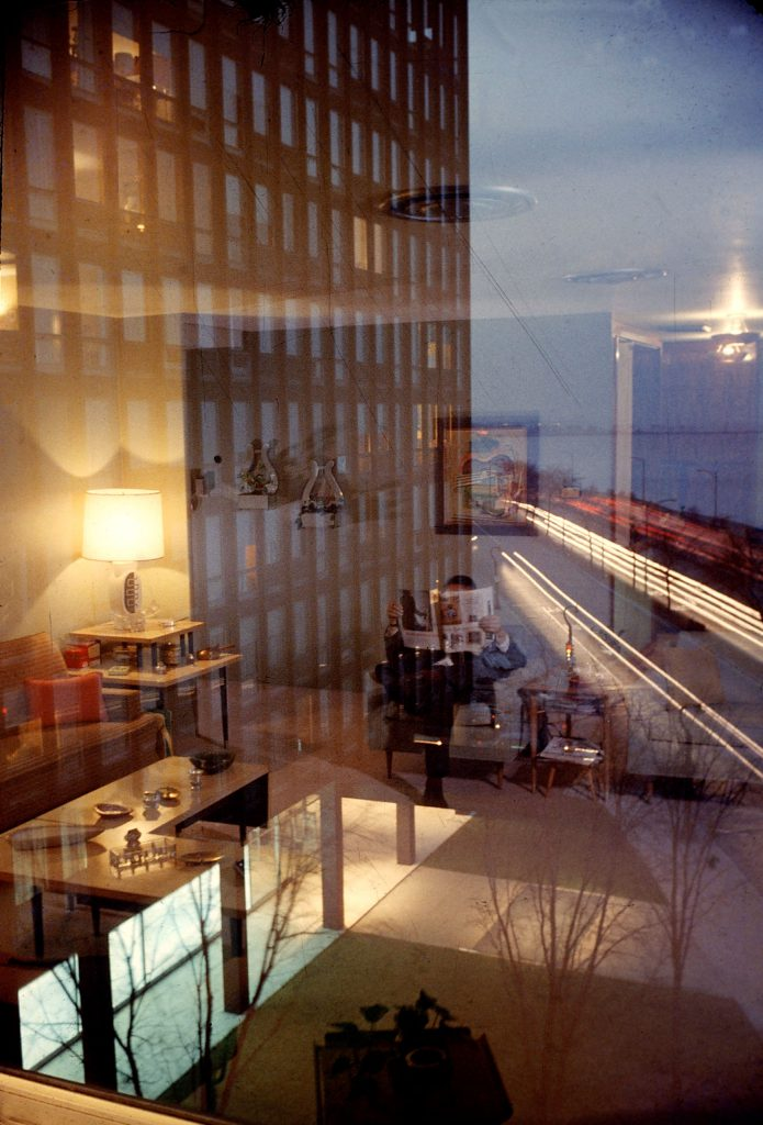 Reflections mirrored in glass wall of an apartment building on Lake Shore Drive building merge like a mirage with outside view of companion building and the lights of traffic.